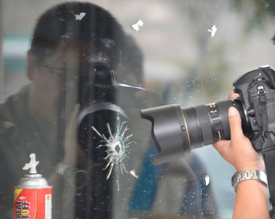 . May 24-,2014. Isla Vista, CA. News cameras gather at IV Deli Mart where bullet holes are seen in the glass windows where one person was killed by the drive-by shooting that left seven people dead Friday night, including the attacker, and seven others wounded, authorities said Saturday.  The gunman got into two gun battles with deputies Friday night in the beachside community of Isla Vista before crashing his black BMW into a parked car. Photo by Gene Blevins/LA Daily News