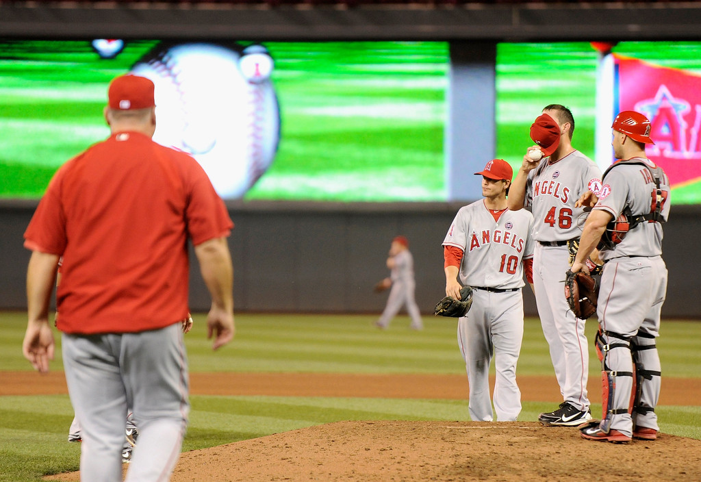 . MINNEAPOLIS, MN - SEPTEMBER 9: Cory Rasmus #46 of the Los Angeles Angels of Anaheim reacts as manager Mike Scioscia #14 makes his way to the mound to remove Rasmus from the seventh inning of the game against the Minnesota Twins on September 9, 2013 at Target Field in Minneapolis, Minnesota. (Photo by Hannah Foslien/Getty Images)