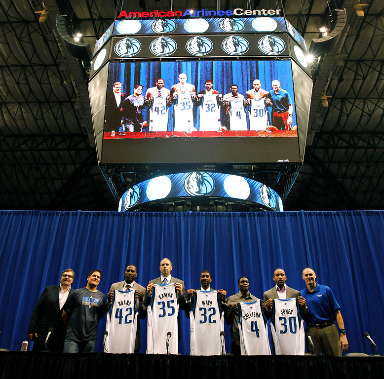 . Dallas Mavericks general manager Donnie Nelson, left, owner Mark Cuban, second from left, and head coach Rick Carlisle, right, pose with Elton Brand (42), Chris Kaman (35), O.J. Mayo (32), Darren Collison (4) and Dahntay Jones (30) during an NBA basketball news conference introducing the new players at American Airlines Center in Dallas, Monday, Sept. 10, 2012. (AP Photo/LM Otero)