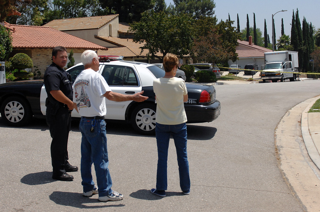 . Neighbors look at the scene on the 19200 block of Kenya Street in Northridge, Friday, June 15, 2013, where a woman was murdered and the suspect surrendered to SWAT officers following a nighttime standoff. (Michael Owen Baker/Staff Photographer)