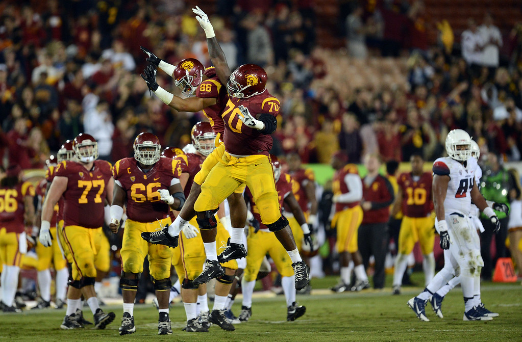 . USC celebrates it\'s win over Arizona during their game at the Los Angeles Memorial Coliseum Thursday, October 10, 2013. USC defeated Arizona 38-31. (Photo by Hans Gutknecht/Los Angeles Daily News)
