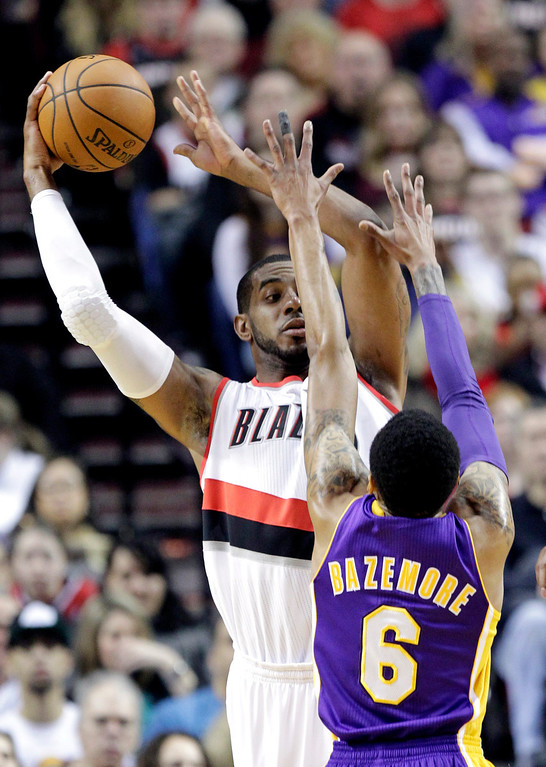 . Portland Trail Blazers forward LaMarcus Aldridge, left, looks for help against the defense of Los Angeles Lakers guard Kent Bazemore during the first half of an NBA basketball game in Portland, Ore., Monday, March 3, 2014. (AP Photo/Don Ryan)