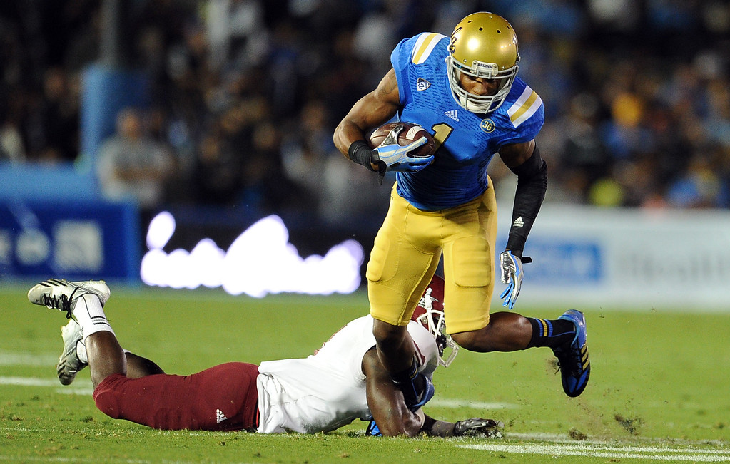 . UCLA wide receiver Shaquelle Evans (1) pulls away from New Mexico State cornerback Darien Johnson (4) for a first down during the first half of their college football game in the Rose Bowl in Pasadena, Calif., on Saturday, Sept. 21, 2013.   (Keith Birmingham Pasadena Star-News)