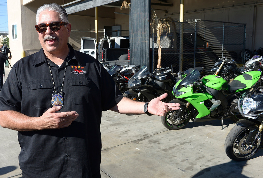 . Detective Jess Corral with recovered bikes. The Taskforce for Regional Autotheft Prevention just broke up a high-end theft/chop shop motorcycle ring. The bikes are parked in a tow yard in North Hollywood, CA. 12/20/2013, photo by (John McCoy/Los Angeles Daily News)