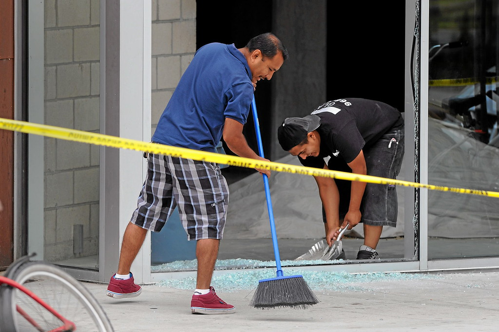 . A work crew cleans up a shot window in front of Peaceful Park at the scene of Friday night\'s shooting in Isla Vista, Saturday, May 24, 2014. (Photo by Michael Owen Baker/Los Angeles Daily News)