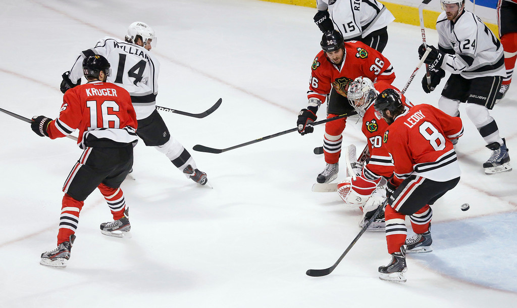 . Los Angeles Kings right wing Justin Williams (14) shoots the puck past Chicago Blackhawks goalie Corey Crawford (50) for a goal during the first period in Game 1 of the NHL hockey Stanley Cup Western Conference finals Saturday, June 1, 2013, in Chicago. (AP Photo/Charles Rex Arbogast)