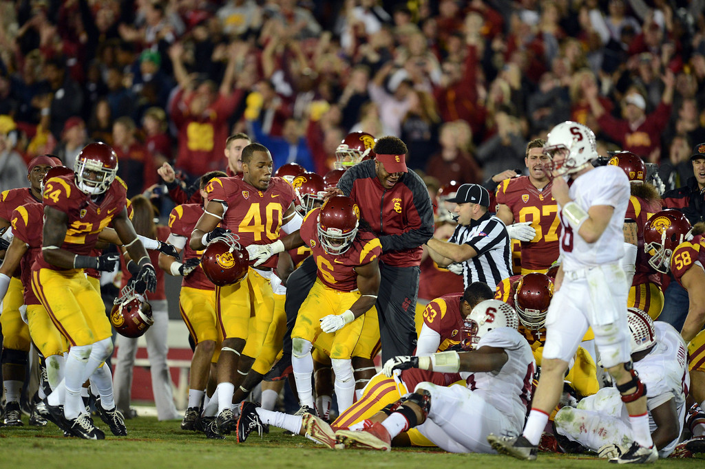 . USC players rush the field as Stanford quarterback Kevin Hogan walks away during their game at the Los Angeles Memorial Coliseum Saturday, November 16, 2013. USC beat Stanford 20-17. (Photos by Hans Gutknecht/Los Angeles Daily News)