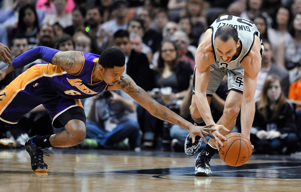 . San Antonio Spurs guard Manu Ginobili, right, comes up with a loose ball in front of Los Angeles Lakers guard Kent Bazemore during the first half of an NBA basketball game Friday, March 14, 2014. (AP Photo/Bahram Mark Sobhani)