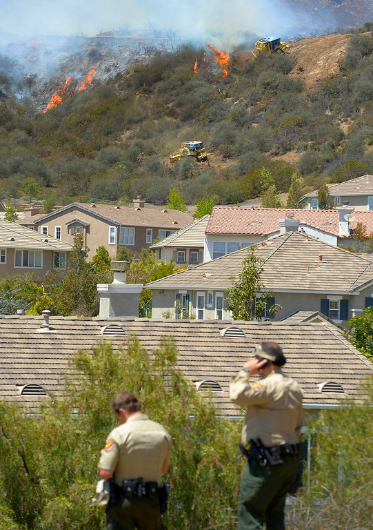 . Sheriff\'s deputies watch as bulldozers clear a firebreak near a wildfire burning along a hillside near homes in Thousand Oaks, Calif., Thursday, May 2, 2013. A Ventura County Fire Department spokeswoman said the blaze that broke out Thursday morning near Camarillo and Thousand Oaks, 50 miles west of Los Angeles, had spread to over 6,500 acres, forcing evacuations of nearby neighborhoods. (AP Photo/Mark J. Terrill)