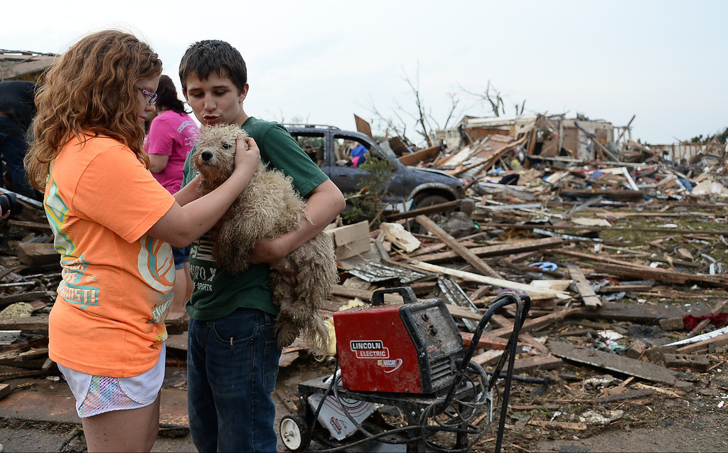 . Peterson Zatterlee and Abby Madi find one of their dogs Rippy among the destroyed buildings and overturned cars. 