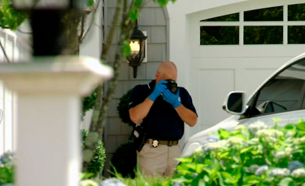 . In this image taken from video,  a police officer photographs a car outside the home of New England Patriots football player Aaron Hernandez, Saturday, June 22, 2013, in North Attleboro, Mass. State police officers and dogs searched Hernandez\'s home as they investigate the killing of Odin Lloyd, a semi-pro football player whose body was found nearby. (AP Photo/ESPN)