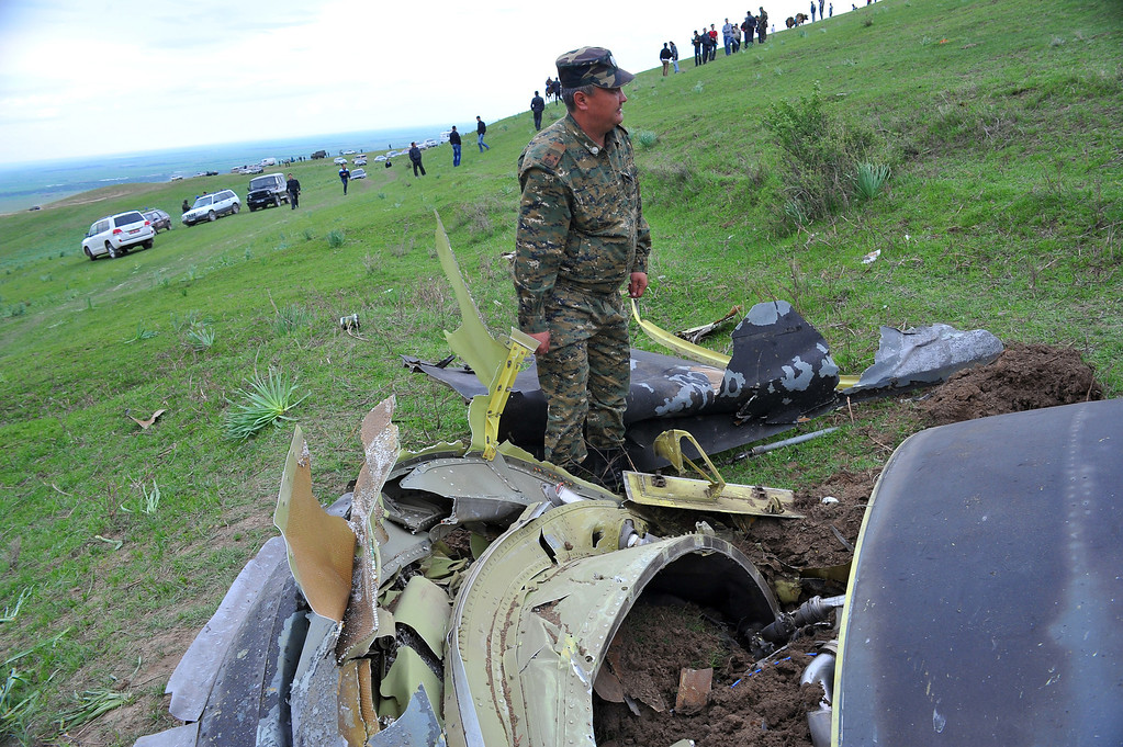 . A soldier stands near the debris of a crashed US KC-135 Stratotanker plane are seen on a hill near the villages of Chorgolo and Cholok-Aryk, Kyrgyzstan. (STRINGER/AFP/Getty Images)