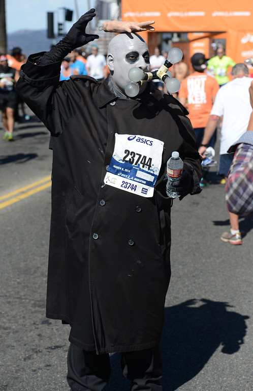 . Some runners wore costumes along Ocean Boulevard, as they crossed the finish line of  2014 ASICS LA Marathon finisher Bill Hopkins after feeling nauseous after he crossed the finish line in Santa Monica Calif,    Sunday, March 9,  2014. 