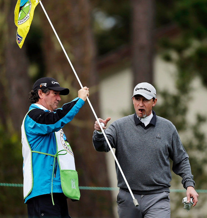 . Hockey great Wayne Gretzky puffs on a cigar as he grabs the pin on the second green of the Monterey Peninsula Country Club Shore Course during the first round of the AT&T Pebble Beach Pro-Am golf tournament, Thursday, Feb. 7, 2013, in Pebble Beach, Calif. (AP Photo/Ben Margot)