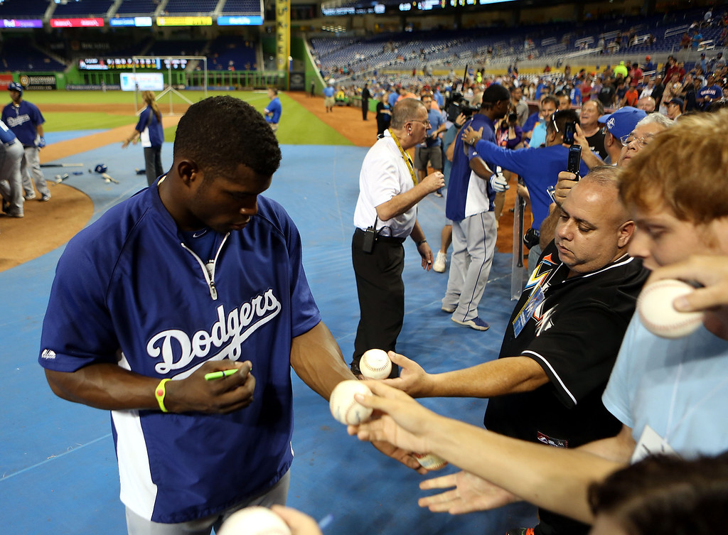 . MIAMI, FL - AUGUST 19: Yasiel Puig #66 of the Los Angeles Dodgers signs autographs prior to playing against the Miami Marlins at Marlins Park on August 19, 2013 in Miami, Florida.  (Photo by Marc Serota/Getty Images)