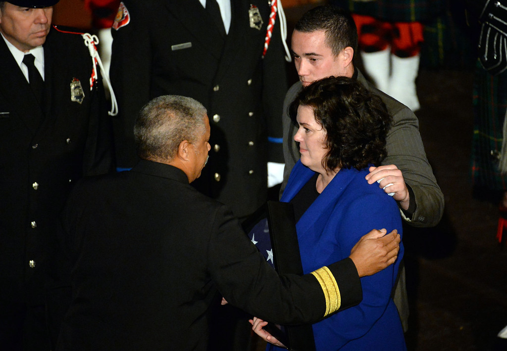 . Shawna Tennant along with brother Brian Tennant receive the flag from Pasadena Fire Chief, Calvin E. Wells, left, during a celebration of life service for former Pasadena Fire dept. Capt. and California State fire marshall, John Tennant at the Pasadena Civic Auditorium in Pasadena, Calif., on Wednesday, Feb. 5, 2014. (Keith Birmingham Pasadena Star-News)