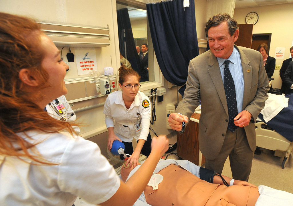 . CSU Chancellor Timothy P. White gives nursing student Victoria Bowman, left, a fist bump after the two tag-teamed to revive a training dummy with CPR. White spent the day touring Cal State Long Beach on Monday, October 14, 2013. 