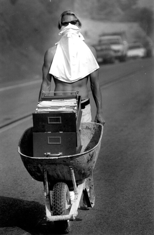 . Wearing a makeshift face mask, a man carts a file cabinet to safety in a wheelbarrow in the Santa Monica Mountains on November 2, 1993.   Los Angeles Daily News file photo