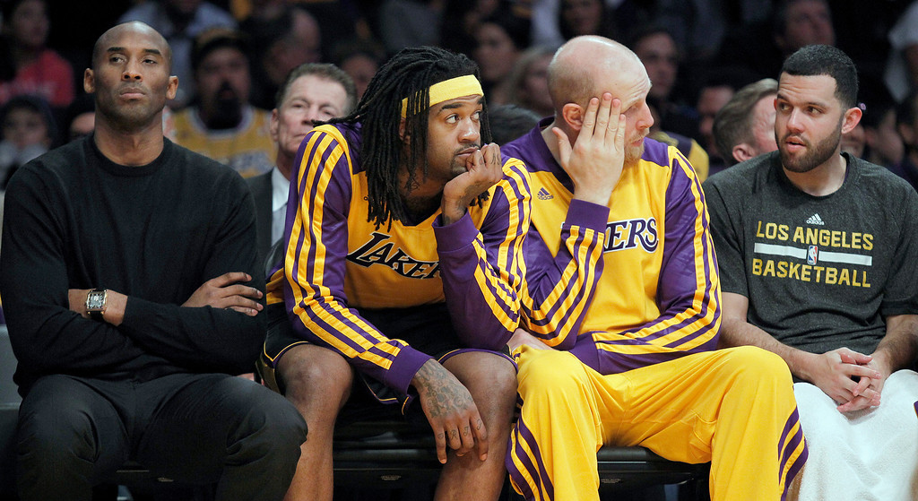 . Los Angeles Lakers injured guard Kobe Bryant, left, center Jordan Hill, second from left, center Chris Kaman and guard Jordan Farmar, right, sit on the bench during the Milwaukee Bucks\' 94-79 win in an NBA basketball game Tuesday, Dec. 31, 2013, in Los Angeles. (AP Photo/Alex Gallardo)