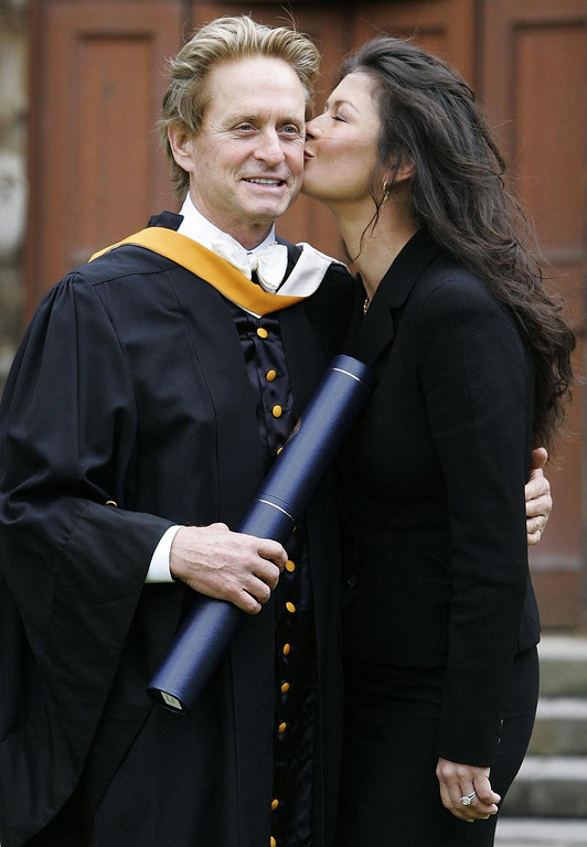 . Hollywood star Michael Douglas receives a kiss from wife Catherine Zeta Jones after collecting his honorary degree at Younger Hall in St Andrews, Scotland Wednesday June 21, 2006. The Oscar-winning American actor received a Doctor of Letters from St Andrews University for his contribution to British film.  (AP Photo/Andrew Milligan, Pool)