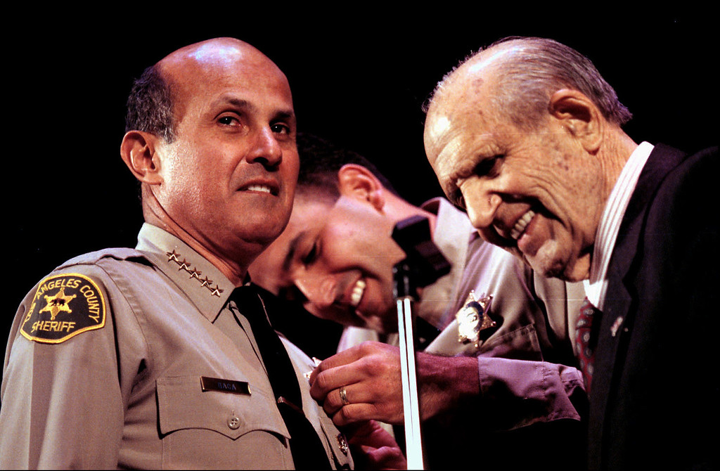 . Sheriff emeritus Peter Pitchess, right, was on hand Monday, December 7, 1998 to pin, with some assistance, the badge on the new Los Angeles county Sheriff Lee Baca during ceremonies at Pasadena Civic Auditorium in Pasadena, Calif. Photo by Leo Jarzomb/San Gabriel Valley Newspaper Group.