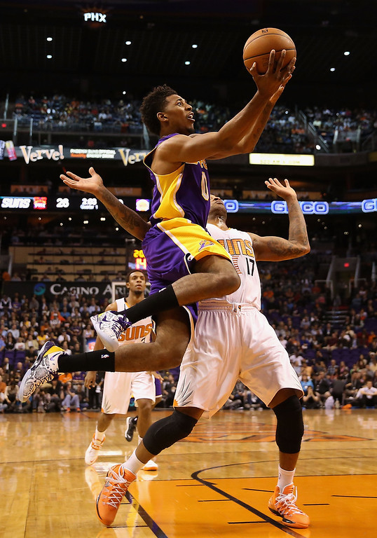 . Nick Young #0 of the Los Angeles Lakers attempts a shot over P.J. Tucker #17 of the Phoenix Suns during the first half of the NBA game at US Airways Center on January 15, 2014 in Phoenix, Arizona.    (Photo by Christian Petersen/Getty Images)
