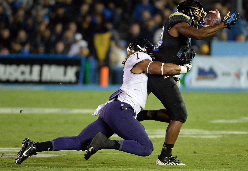 . Washington Huskies\'s Sean Parker (1) tackles UCLA Bruins running back Paul Perkins (24) as he drops the pass during the first half of their college football game in the Rose Bowl in Pasadena, Calif., on Friday, Nov. 15, 2013.  UCLA won 41-31. 