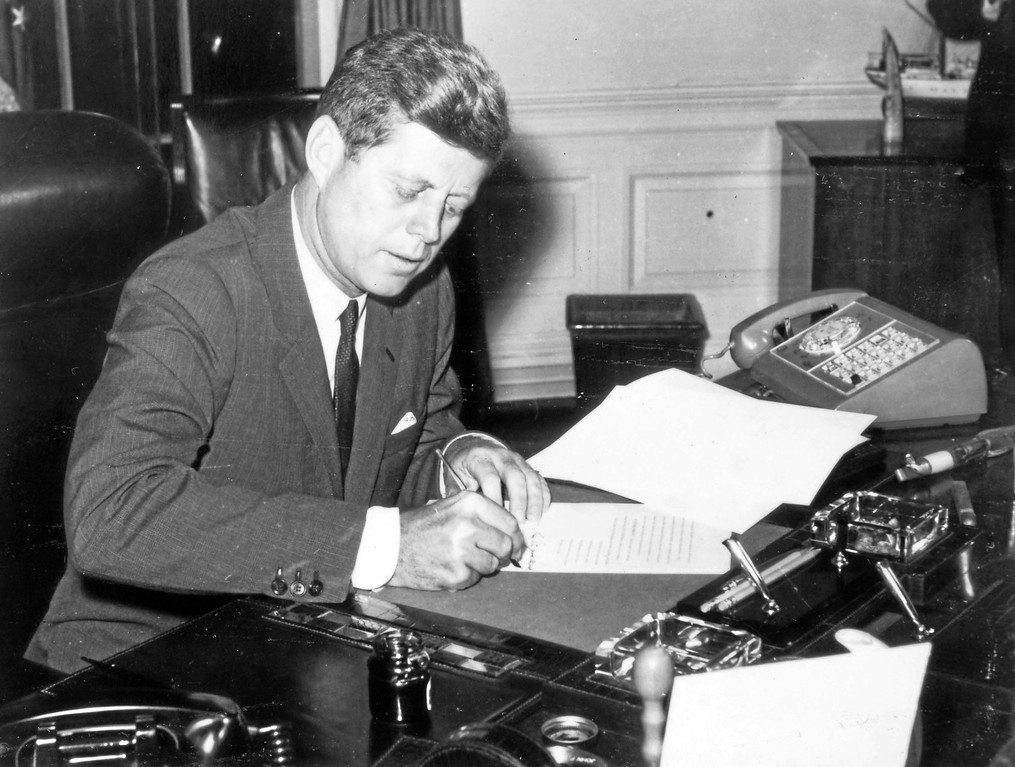 . John F. Kennedy at his desk.