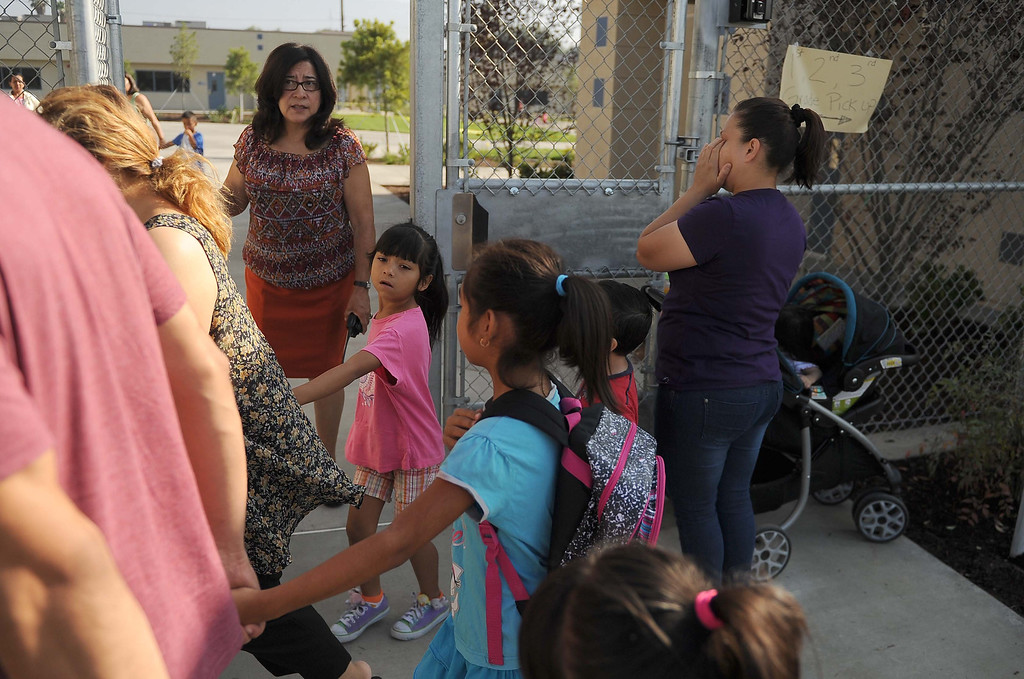 . Principal Socorro Gomez- Potter, welcome students walks to classes at the new Graciano Gomes Elementary Tuesday August 9, 2013  in San Bernardino.LaFonzo Carter/ Staff Photographer