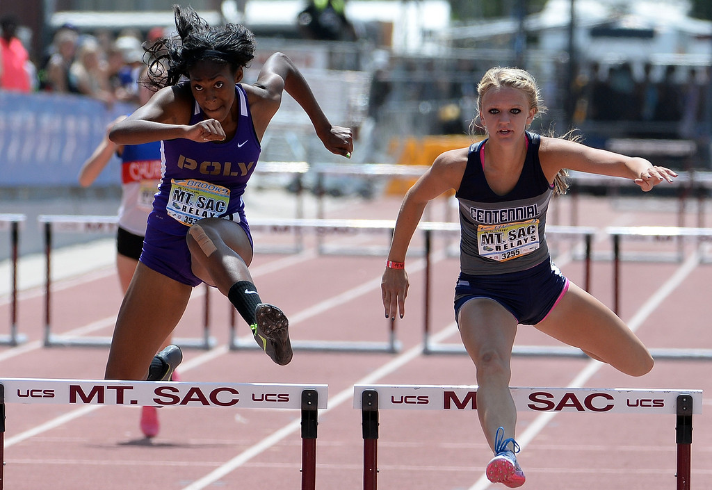 . Long Beach Poly\'s Ebony Crear, left, along with Centennial\'s Tiana Bonds in the 300 meter hurdles Invitational during the Mt. SAC Relays in Hilmer Lodge Stadium on the campus of Mt. San Antonio College in Walnut, Calif., on Saturday, April 19, 2014. 