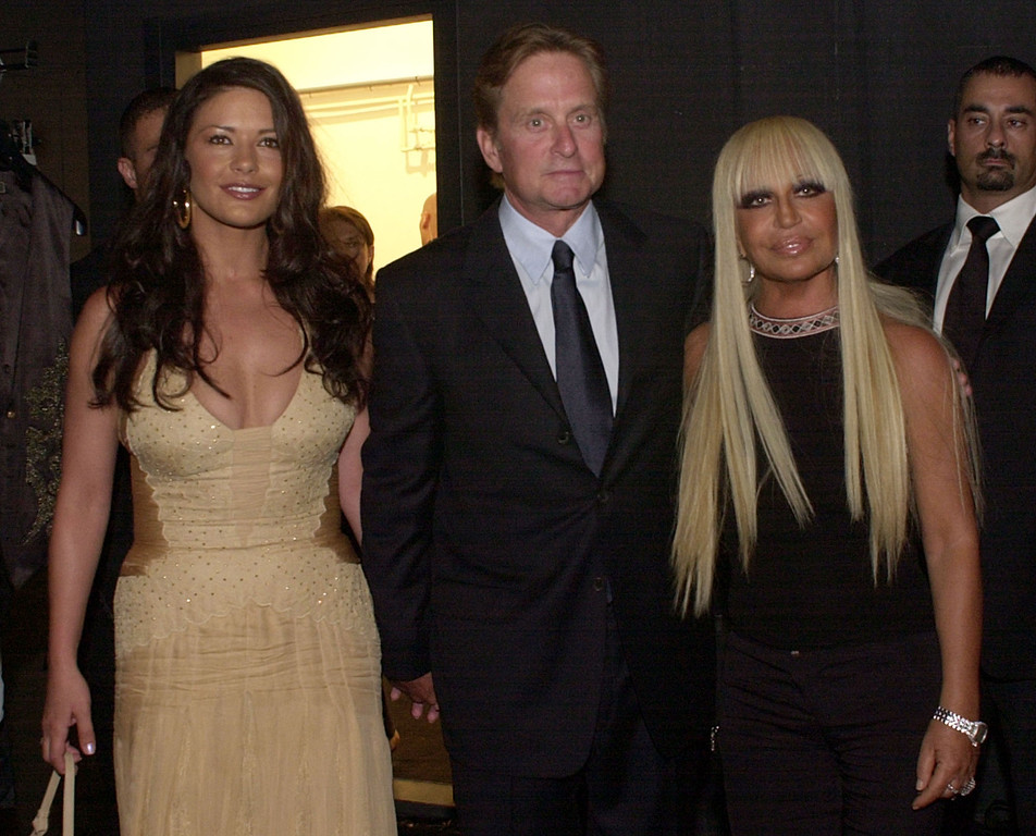 . U.S. actor Michael Douglas, center, his wife Catherine Zeta Jones, left, and fashion designer Donatella Versace pose prior to the Gianni Versace Spring-Summer 2004 men\'s fashion collection, presented in Milan, Italy, Sunday, June 22, 2003. (AP Photo/Antonio Calanni)