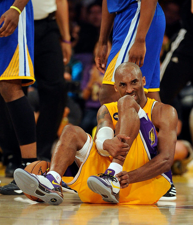 . The Lakers\' Kobe Bryant #24 sits on the court after hurting his ankle during their game against the Warriors at the Staples Center in Los Angeles Friday, April 12, 2013. The Lakers beat the Warriors 118-116. (Hans Gutknecht/Los Angeles Daily News)