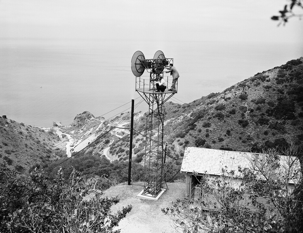 . Richard L. Hayes (left) and Byron Graff, repairmen for the Southern California Telephone Company, are shown on the top of the tower which will be used in connection with the new micro-wave radio radio telephone between Catalina Island and Los Angeles in Catalina Island. When placed into service, this new system will add eight talking circuits to the 15 now operating over submarine telephone cables. (AP Photo)