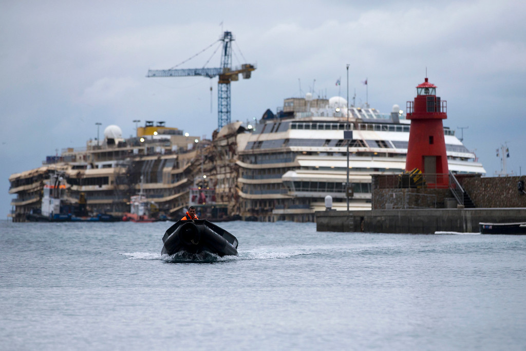 . A rubber dinghy returns to the port as the shipwreck of the Costa Concordia cruise ship is seen in the background, in the Giglio Island port, Wednesday, Feb. 26, 2014. The captain of the Costa Concordia has been permitted to go aboard the shipwreck for the first time since it capsized two years ago as part of a new court-ordered search. Consumer groups and lawyers for Capt. Francesco Schettino asked the court in Grosseto to authorize the searches to determine if any factors beyond human error contributed to the disaster. After searching the bridge and elevators last month, experts will examine the emergency generators Thursday. (AP Photo/Andrew Medichini)
