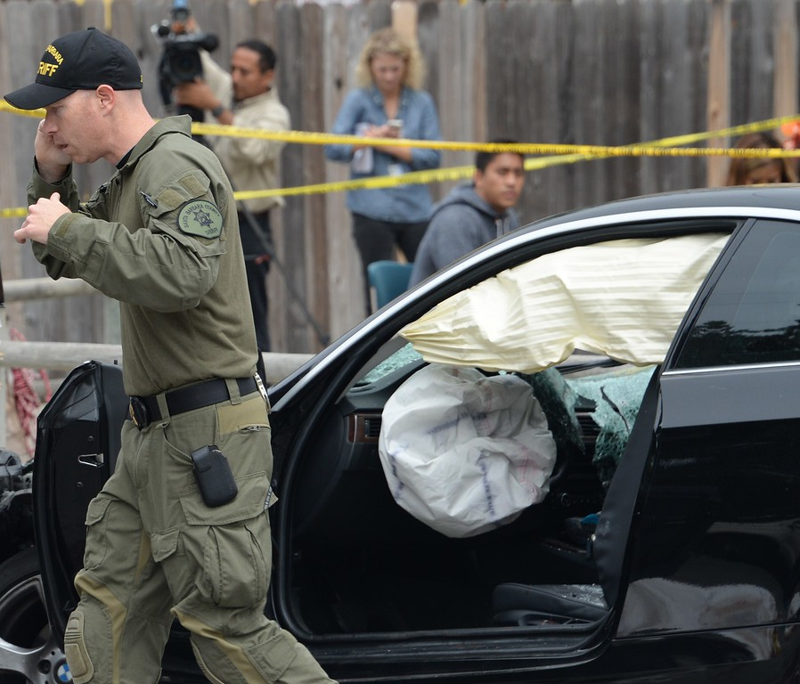 ". An investigator speaks on a cell phone while inspecting a suspected gunman\'s car on May 24, 2014, after a drive-by shooting in Isla Vista, California, a beach community next to the University of California Santa Barbara. Seven people, including the gunman, were killed and seven others wounded in the May 23 mass shooting, Santa Barbara County Sheriff Bill Brown said Saturday. Brown said at a pre-dawn press conference that the shooting in the town of Isla Vista ""appears to be a mass murder situation.\"" Driving a black BMW, the suspect opened fire on pedestrians from his vehicle at several locations in the town.            (ROBYN BECK/AFP/Getty Images)"