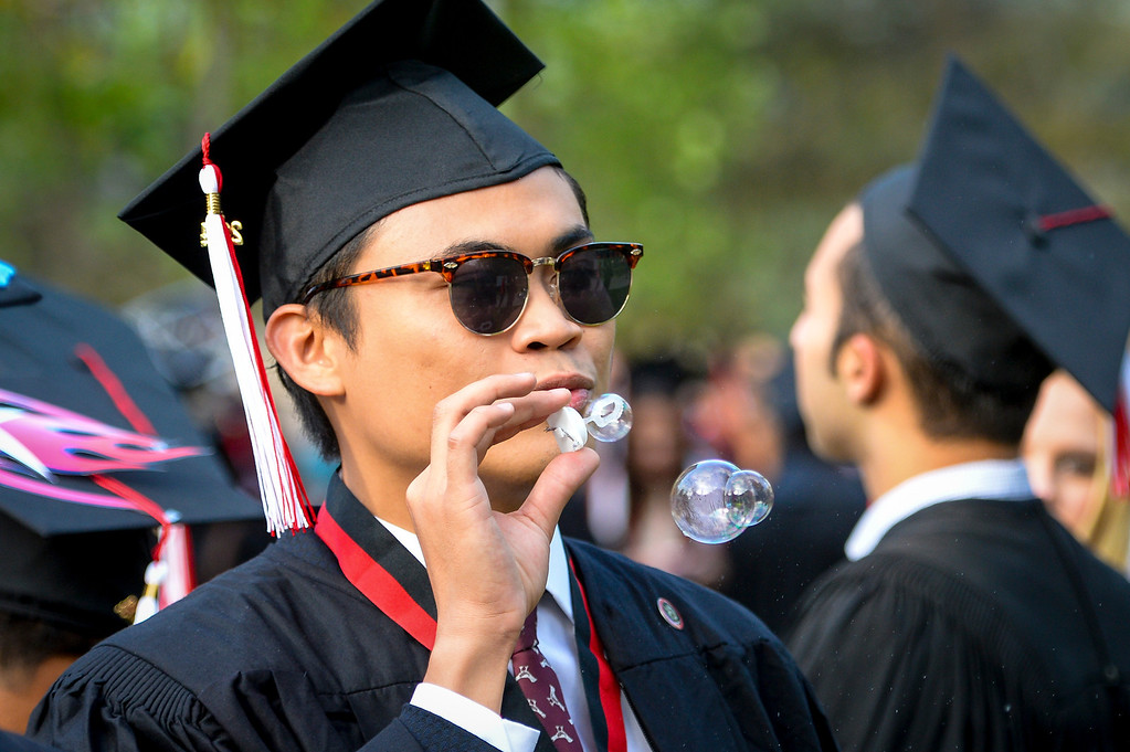 . Carlo Maghirang blows bubbles as he waits for the start of  graduation ceremonies at Cal State Northridge Monday, May 19, 2014.  ( Photo by David Crane/Los Angeles Daily News )