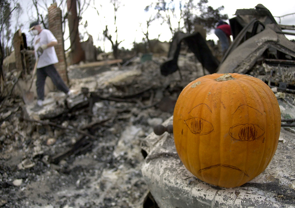 . Dale Foster walks past a decorated pumpkin as he searches for slavageable items in his burned-out home in the Scripps Ranch area of San Diego, Calif. Thursday, Oct. 30, 2003. The home was among more than 1,500 lost in the 275,000 acre Cedar fire. (AP Photo/Charlie Riedel)