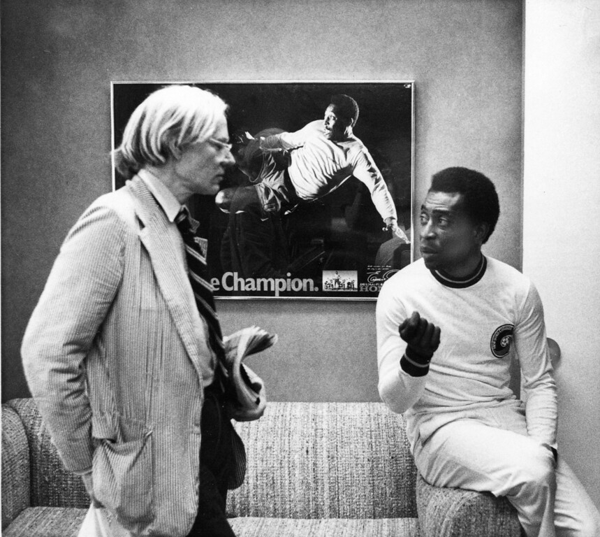 . Artist Andy Warhol, left, chats to soccer superstar Pele about a portrait he is making of him. In background is a poster with a photograph of Pele in action. Warhol has been commissioned to make a series of portraits of athletic stars. New York, July. 26, 1977. (AP Photo/Claudia Larson)
