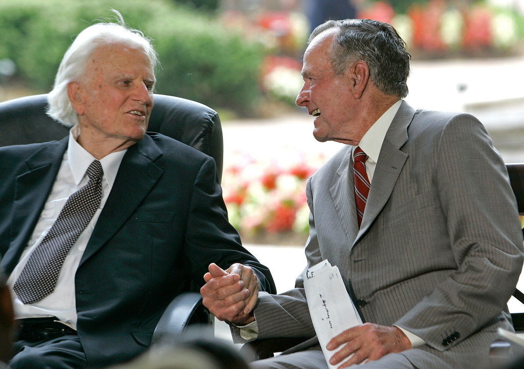 . Former President George H.W. Bush, right, takes Billy Graham\'s hand during a ceremony for the Billy Graham Library in Charlotte, N.C., Thursday, May 31, 2007. (AP Photo/Gerry Broome)