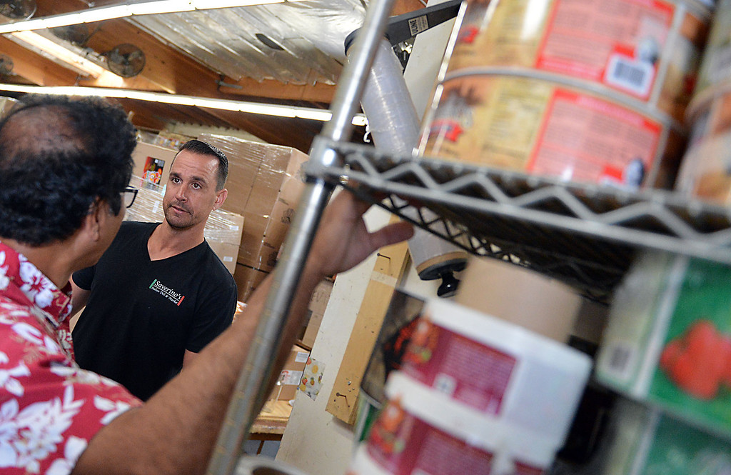 . David Saverino, right, and Freddie Damo owner of Da\'Kine Foods in Newport Beach look over Saverino\'s lable for his sauce being bottled at Da\'Kine Foods. Following the successful launch of Saverino\'s Italian Deli and Market in Redlands nearly two years ago, David Saverino is bottling the flavor of his business with the introduction of four separate sauces. In addition to selling the sauces at his deli, Saverino hopes to see his product on the shelves of local markets. (Photo by Rick Sforza/Redlands Daily Facts)