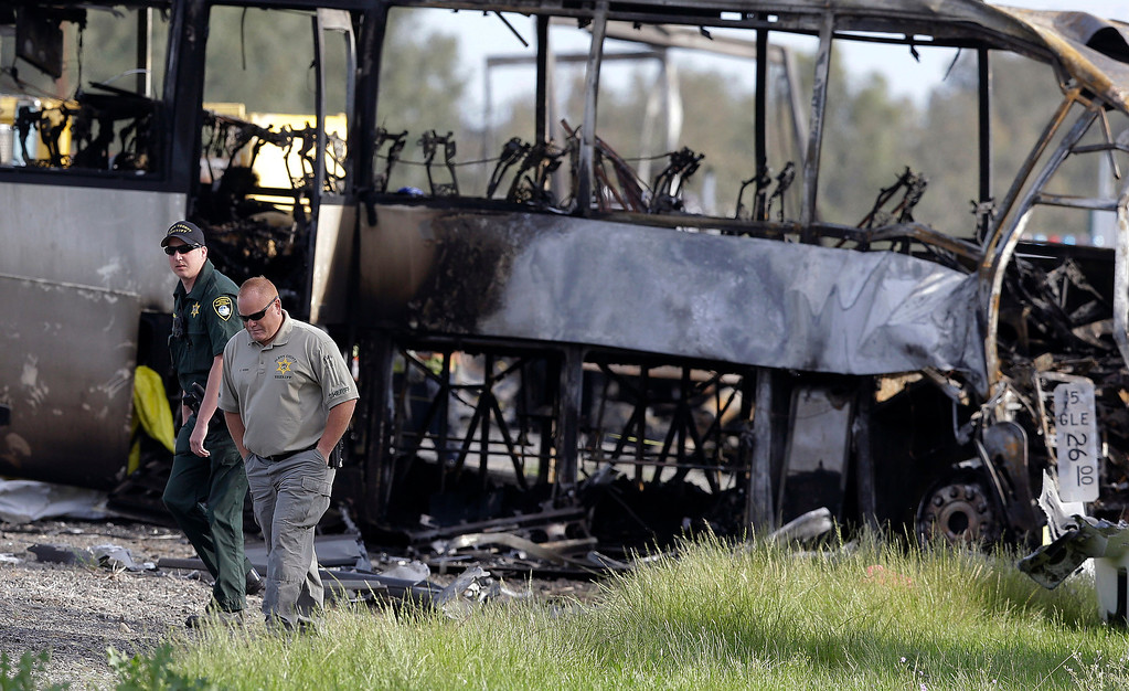 . Glenn County Sheriff\'s officers walk past the remains of a tour bus that was struck by a FedEx truck on Interstate 5 Thursday in Orland, Calif., Friday, April 11, 2014. At least ten people were killed and dozens injured in the fiery crash between the truck and a bus carrying high school students on a visit to a Northern California College. (AP Photo/Jeff Chiu)