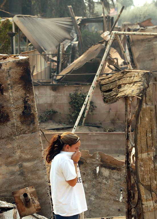 . Ten years ago this month the arson caused Old Fire, fanned by Santa Ana winds burned thousands of acres, destroyed hundreds of homes and caused six deaths. The fire burned homes in San Bernardino, Highland, Cedar Glen, Crestline, Running Springs and Lake Arrowhead and forced the evacuation of thousand of residents. Barbara Padilla, 17, covers her nose while watching her father sift through the rubble of their home at 3995 La Hacienda Dr. in San Bernardino after it was destroyed by the Old Fire. (Staff file photo/The Sun)