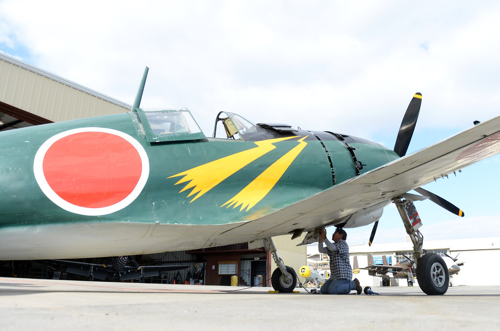 """. John Kagihara, aircraft mechanic for Planes of Fame Air Museum, works on a Mitsubishi J2M Raiden, used by the Imperial Navy during World War II, Friday, Dec. 6, 2013 in Chino. The Museum will present �Attack on Pearl Harbor\' for its monthly Living History Event, which guest speaker Dan king author of the book \""""The Last Zero Fighter\"""". (John Valenzuela/Staff Photographer)"""