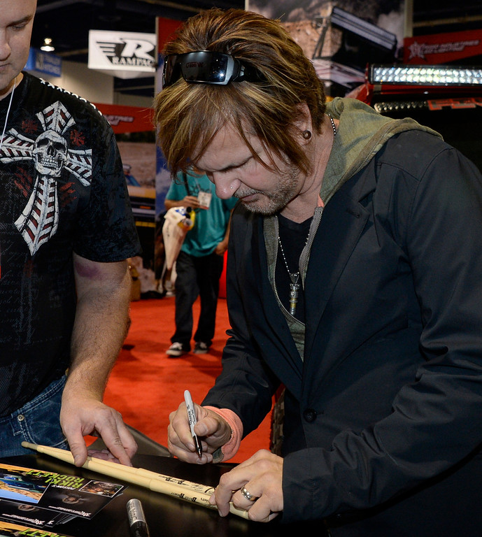 . Nov 6,2013 Las Vegas NV. USA. 1980s Poison drummer Rikki Rocket signs autographs at the Rigid LED lighting booth during the second day of the 2013 SEMA auto show.