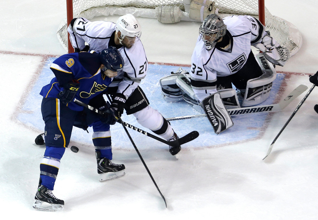 . St. Louis Blues\' Jaden Schwartz (9) tries to control the puck as Los Angeles Kings\' Alec Martinez and goalie Jonathan Quick, right, defend during the first period in Game 5 of a first-round NHL hockey Stanley Cup playoff series, Wednesday, May 8, 2013, in St. Louis. (AP Photo/Jeff Roberson)