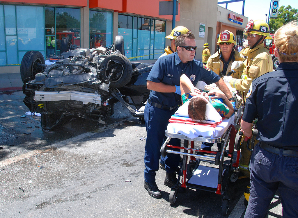 . North Hollywood, Ca LAFD firefighters work on a female victim of a three car accident at lankershim Bl and Vineland Av this afternoon. One was killed in the SUV to the left and 4 others were transported to local hospitals in conditions from moderate to serious. LAPD are on the scene and investigating. Firefighters said there were many beer cans in the overturned SUV...