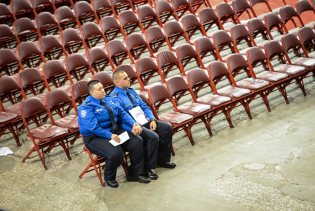 . LAX TSA supervisory officers Danielle Arocho and Lisandro Jimenez sit together alone after the memorial for slain TSA officer Gerardo Hernandez at the Los Angeles Sports Arena Tuesday, November 12, 2013.  A public memorial was held for Officer Hernandez who was killed at LAX when a gunman entered terminal 3 and opened fire with a semi-automatic rifle.  ( Photo by David Crane/Los Angeles Daily News )