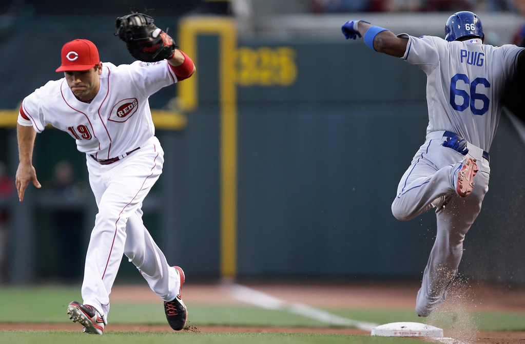 . Los Angeles Dodgers\' Yasiel Puig (66) is safe at first with an infield single as Cincinnati Reds first baseman Joey Votto (19) is pulled off the bag by a wide throw from shortstop Zack Cozart in the first inning of a baseball game, Friday, Sept. 6, 2013, in Cincinnati. (AP Photo/Al Behrman)