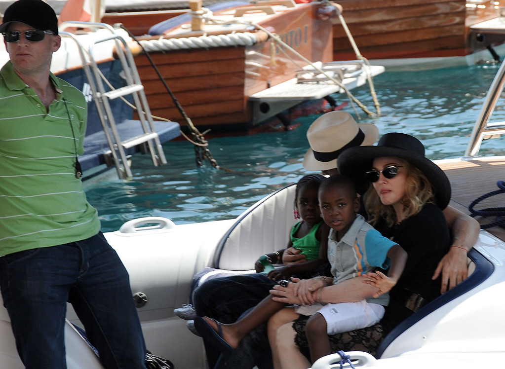 ". Photo taken Monday Aug. 17, 2009 made available Tuesday Aug. 18, 2009 of U.S. singer Madonna, at right, with her adopted child from Malawi David Banda, waving, and Brazilian model Jesus Luz, background with havana hat, holding her other adopted child Chifundo ""Mercy\"" James, on a speedboat on their way to see friends on a yacht, in Italy\'s northwestern riviera town of Portofino. Man at left is unidentified. Reports said Tuesday Madonna is in the seaside resort town to spend some time with Italian designers Dolce and Gabbana and other friends. After adopting David Banda in 2008, Malawi\'s highest court had granted the adoption of Chifundo \""Mercy\"" James June 12, 2009 overturning an April lower court ruling that Madonna had not spent enough time in Malawi to be given a child. Madonna\'s Raising Malawi, a charity founded in 2006, helps feed, educate and provide medical care for some of Malawi\'s orphans.  (AP Photo)"