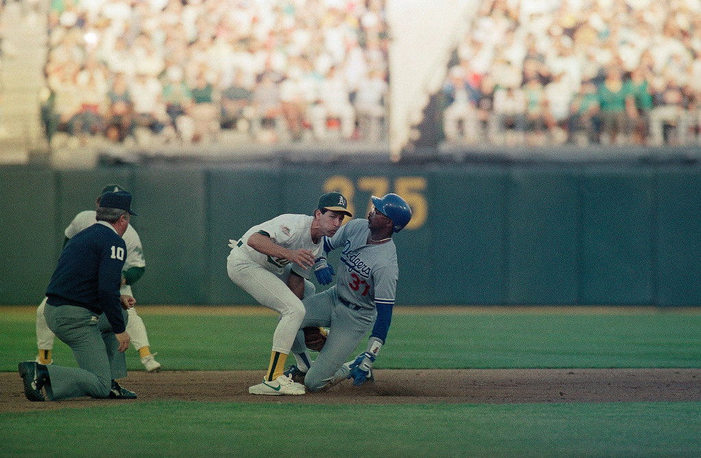 . Los Angeles Dodgers Mike Davis slides safely into second base with a steal as Oakland A\'s shortstop Walt Weiss applies the late tag in the first inning of the fourth game of the World Series in Oakland Coliseum, Wednesday, Oct.19, 1988. (AP Photo/Lennox Mclendon)